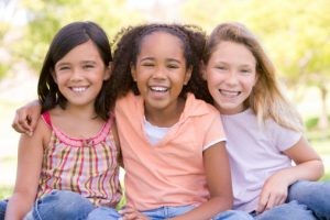 three young girls with beautiful smiles thanks to the washington kids dentist