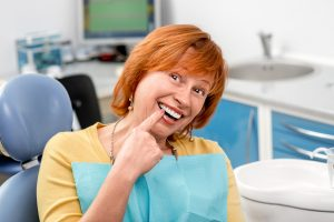 senior woman pointing to replacement tooth