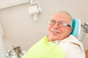 older man smiling sitting in dentist chair