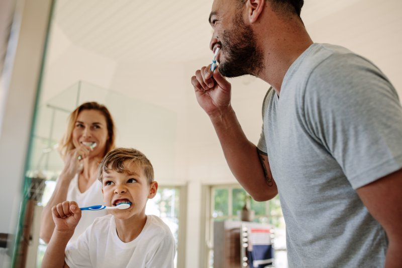 Family smiling while brushing their teeth together